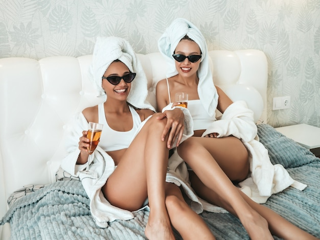 Two young beautiful smiling women in white bathrobes and towels on head