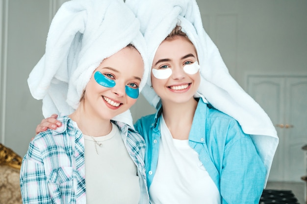 Two young beautiful smiling women with patches under their eyes