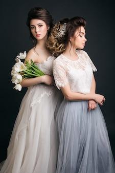 Two young beautiful stylish women in wedding dresses