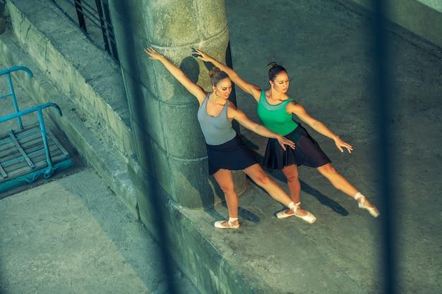 バレエ衣装で街でバレエを踊る2人の若い美しい双子の姉妹。アーバンシンクダンス。インダストリアルストリートダンス。特殊効果付き。同期ポーズ。トウシューズとドレス。