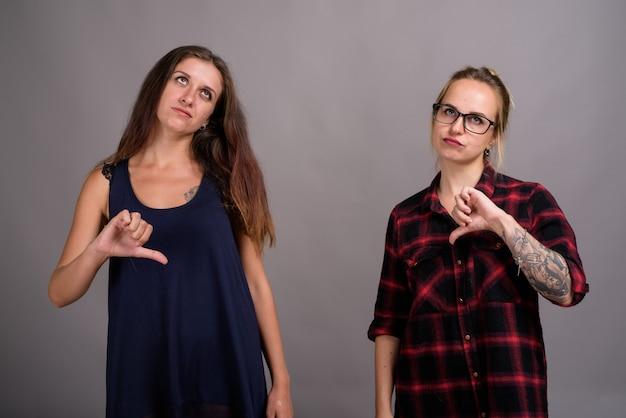Две молодые красивые подруги вместе на сером