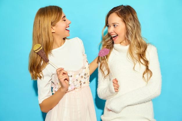 Две молодые красивые женщины поют с реквизита поддельные микрофона. модные женщины в повседневной летней одежды. смешные модели, изолированные на синей стене
