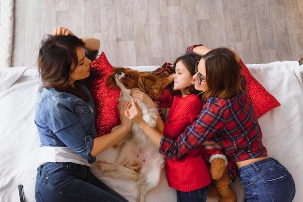 2人の若い美しい女性と女の子がクリスマスツリーの近くの自宅のベッドに横たわっています