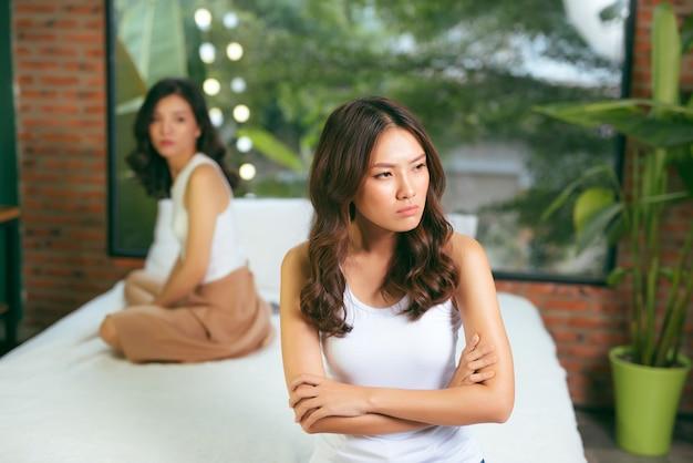 家でお互いに怒っている2人の若い美しい女性