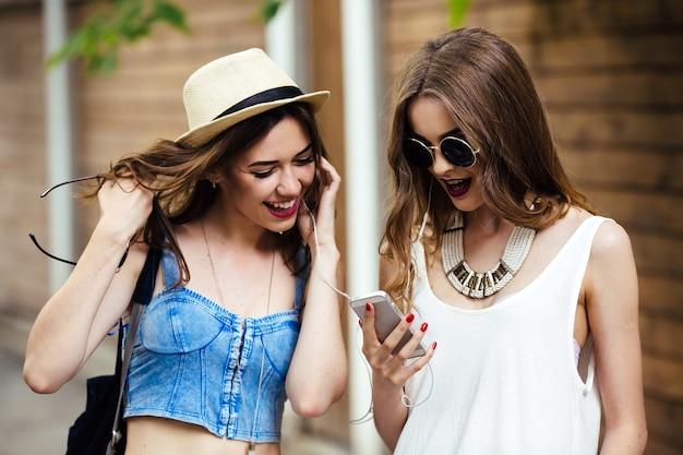 두 젊은 아름다운 여성이 도시를 걷고 음악을 듣고