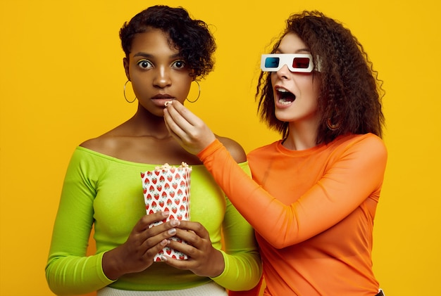 Two young beautiful women in colorful summer clothes eating popcorn