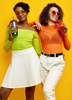 Two young beautiful women in colorful summer clothes with cocktails