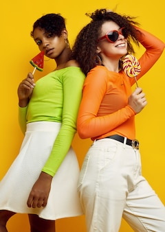 Two young beautiful women in colorful summer clothes with lollipops