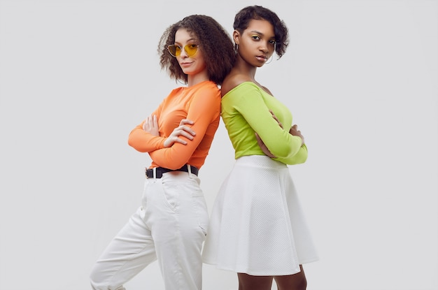 Two young beautiful women in colorful summer clothes