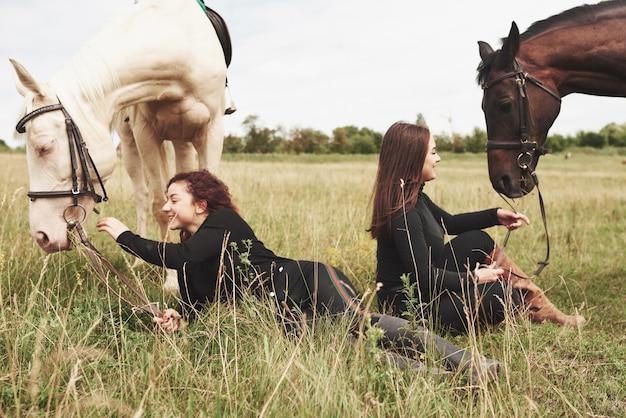 彼らの馬の近くに乗るためのギアの2人の若い美しい女性。彼らは動物が大好き