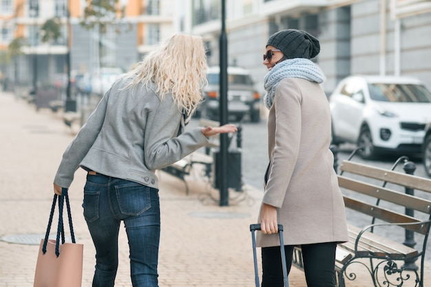 暖かい服を着て歩く2人の若い美しい女性