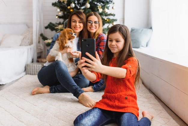 Two young beautiful women and little girl while celebrating christmas at home