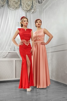Two young, beautiful women in long, evening red and peach dresse