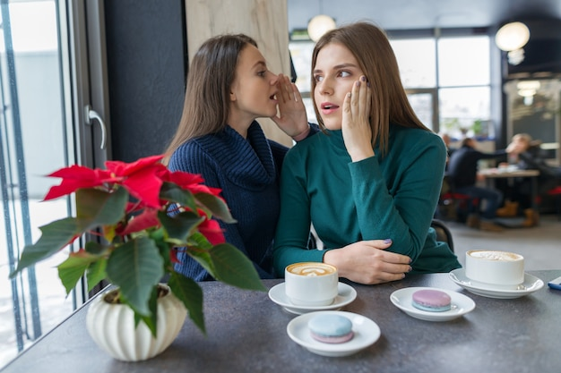 Two young beautiful women secretly