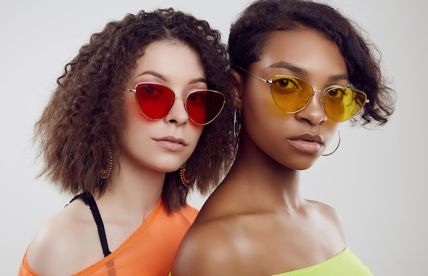 Two young beautiful women in summer clothes and bright sunglasses