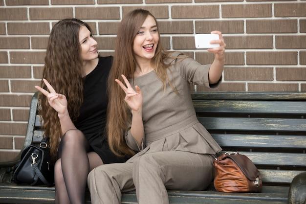 2人の若い美しい女性が通りにセルフをしています