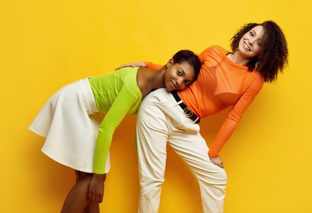 Two young beautiful women in trendy colorful summer clothes