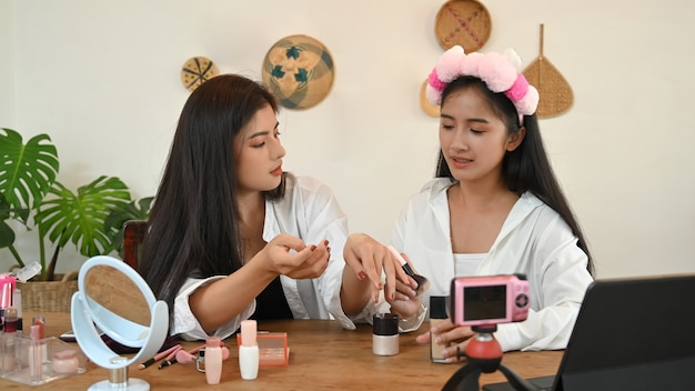 Two young beauty bloggers recording video at home.