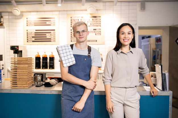 Two young best waiters of luxurious restaurant or cafe standing by counter while meeting new guests