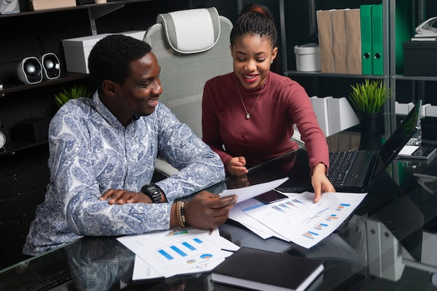 Two young black people discuss their business using diagrams sitting at desk