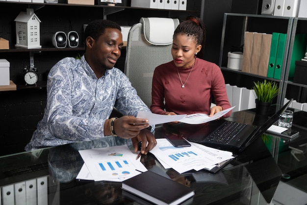 Two young black people discuss their business using diagrams sitting