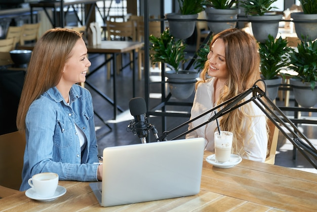 Two young blogger women talking with followers online