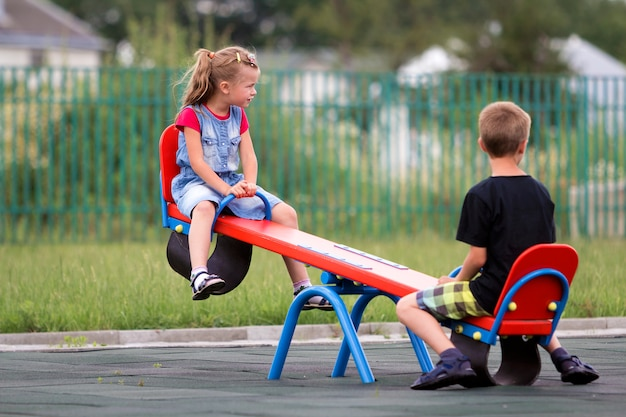 Two young blond preschoolers swing on seesaw
