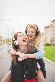 Two young blonde and brunette girls listening to music in the city