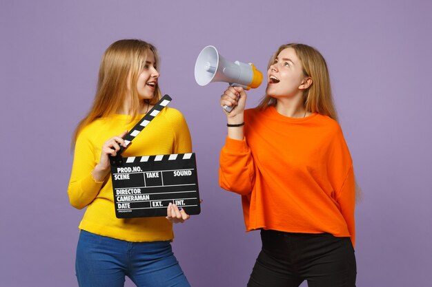 Две молодые белокурые девушки сестры-близнецы держат классический черный фильм, делая с 'хлопушкой', кричат на мегафон, изолированный на пастельно-фиолетовой синей стене. концепция семейного образа жизни людей.