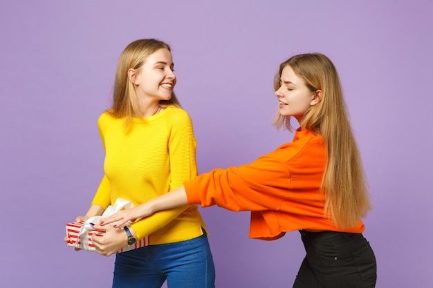 화려한 옷을 입고 두 젊은 금발 쌍둥이 자매 소녀 보라색 파란색 벽에 고립 된 선물 리본이 달린 빨간색 줄무늬 선물 상자를 개최합니다. 사람들이 가족 생일, 휴가 개념.