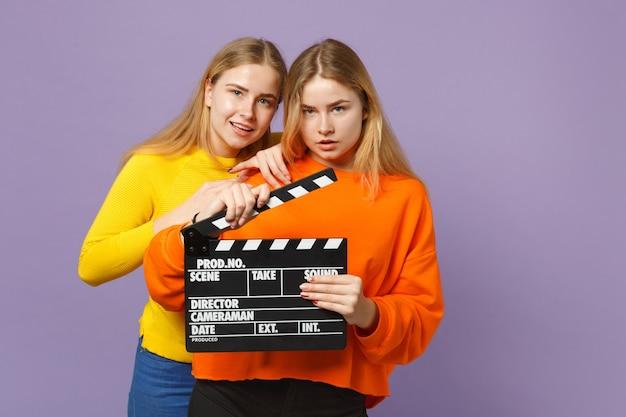 파스텔 바이올렛 블루 벽에 고립 된 clapperboard 만들기 클래식 블랙 영화를 들고 화려한 옷에 두 젊은 금발 쌍둥이 자매 소녀. 사람들이 가족 라이프 스타일 개념. .