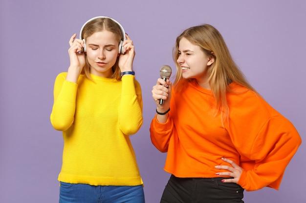 Две молодые блондинки сестры-близнецы девушки в яркой одежде слушают музыку в наушниках, поют песню в микрофон, изолированные на фиолетово-синей стене. концепция семейного образа жизни людей.