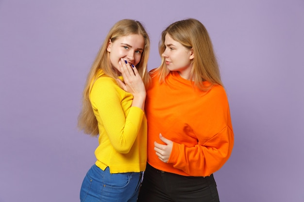 パステルバイオレットブルーの壁に隔離された手で口を震わせながら、お互いを見つめているカラフルな服を着た2人の若い金髪の双子の姉妹の女の子。人々の家族のライフスタイルの概念。