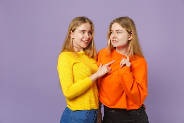 パステルバイオレットブルーの壁に分離された人差し指を指して、お互いを見つめているカラフルな服を着た2人の若い金髪の双子の姉妹の女の子。人々の家族のライフスタイルの概念。