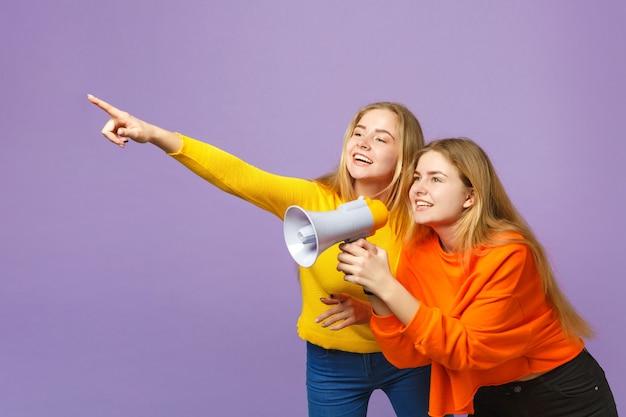 パステルバイオレットブルーの壁に分離されたメガホンで人差し指を脇に向けてカラフルな服を着た2人の若いブロンドの双子の姉妹の女の子が悲鳴を上げます。人々の家族のライフスタイルの概念。