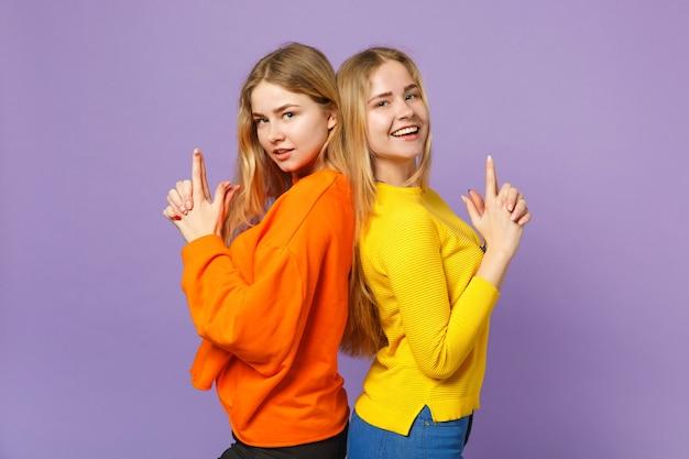 파스텔 바이올렛 블루 벽에 고립 된 총 같은 손가락을 유지, 연달아 서 화려한 옷을 입고 두 젊은 금발 쌍둥이 자매 소녀. 사람들이 가족 라이프 스타일 개념.