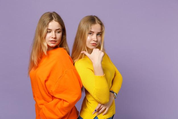 화려한 옷을 입고 두 젊은 금발 쌍둥이 자매 여자 다시 다시 파스텔 바이올렛 파란색 벽에 고립 된 엄지를 제쳐두고 가리키는 서. 사람들이 가족 라이프 스타일 개념.