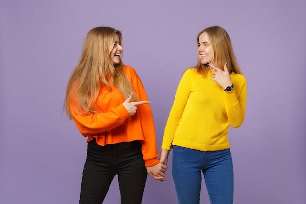 パステルバイオレットブルーの壁に隔離された人差し指を互いに指している鮮やかな服を着た2人の若い金髪の双子の姉妹の女の子。人々の家族のライフスタイルの概念。