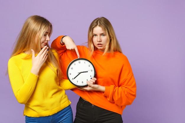 パステルバイオレットブルーの壁に分離された丸い時計に人差し指を指している鮮やかなカラフルな服を着た2人の若いブロンドの双子の姉妹の女の子。人々の家族のライフスタイルの概念。