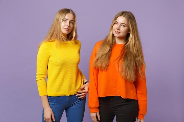 파스텔 바이올렛 파란색 벽에 고립 된 서 생생한 화려한 옷을 입고 두 젊은 금발 쌍둥이 자매 여자. 사람들이 가족 라이프 스타일 개념.