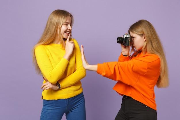 Две молодые белокурые девушки сестры-близнецы в яркой красочной одежде фотографируют на ретро-винтажную фотокамеру, изолированную на фиолетово-синей стене. концепция семейного образа жизни людей.