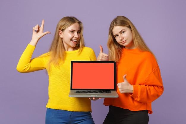 2人の若いブロンドの双子の姉妹の女の子が人差し指を上に向けて、パステルバイオレットブルーの壁に分離された空白の空の画面でラップトップpcコンピューターを保持します。人々の家族のライフスタイルの概念。 。
