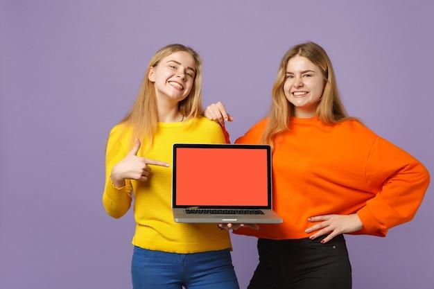 パステルバイオレットブルーの壁に分離された空白の空の画面でラップトップpcコンピューターに人差し指を指している2人の若いブロンドの双子の姉妹の女の子。人々の家族のライフスタイルの概念。 。