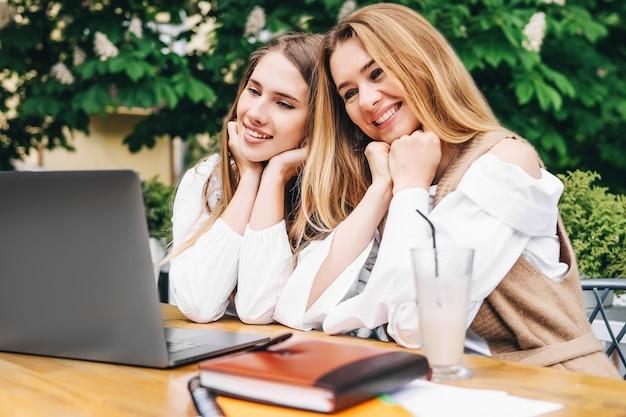 두 젊은 금발 여성이 테이블에 앉아 미소를 지으며 컴퓨터를 보고 있습니다