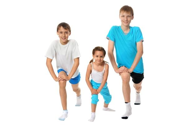 白い背景で隔離の運動をしている2人の若い男の子の兄弟と妹