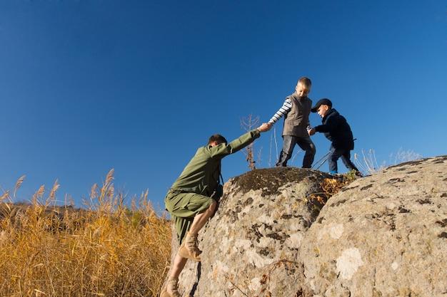 정찰병이 바위 절벽을 오르는 것을 돕는 두 소년