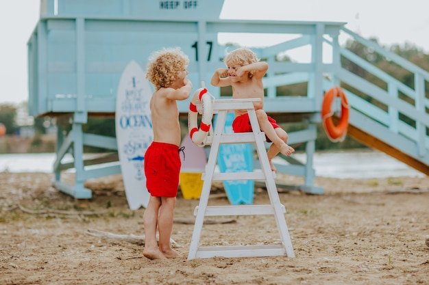 赤い水泳パンツ姿の2人の少年と、ビーチの監視員の椅子に座っている1人の少年