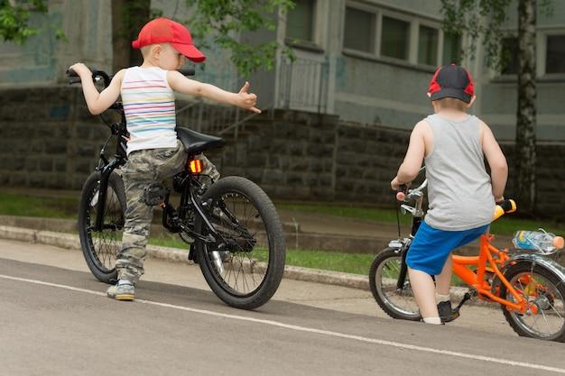 도시 환경에서 길가에서 자전거를 타고 함께 노는 두 어린 소년