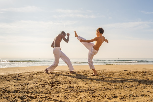 Two young brazilian in white pants practicing capoeira (brazilian martial art that combines elements of dance, acrobatics and music) on the beach