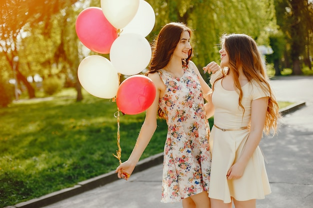 Two young and bright girls spend their time in the summer park with balloons